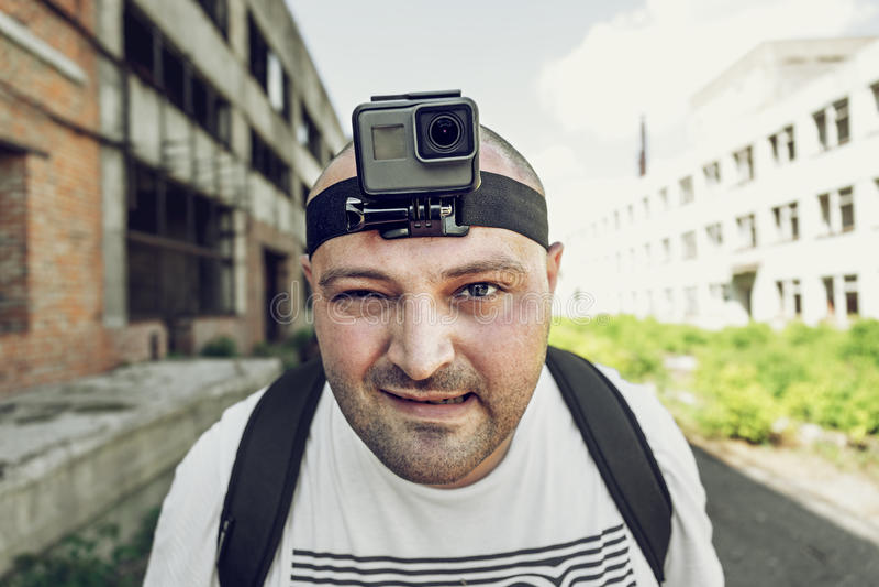 L'uomo arrabbiato con la macchina fotografica di azione sulla testa che esamina la macchina fotografica e va Ritratto del blogger fotografia stock