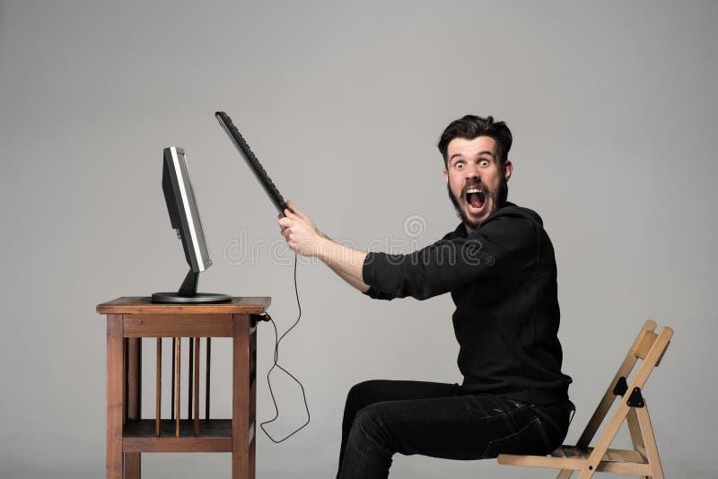 L'uomo arrabbiato sta distruggendo una tastiera immagine stock libera da diritti