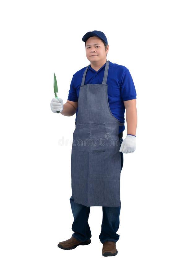 L'uomo asiatico del lavoratore in camicia blu con il grembiule ed i guanti protettivi passano la pala della tenuta isolata su bia fotografia stock