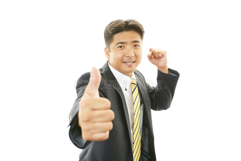 L'uomo asiatico felice di affari che mostra i pollici aumenta il segno immagine stock libera da diritti