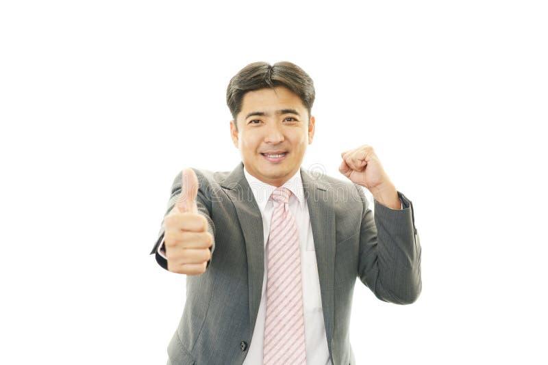L'uomo asiatico felice di affari che mostra i pollici aumenta il segno fotografia stock