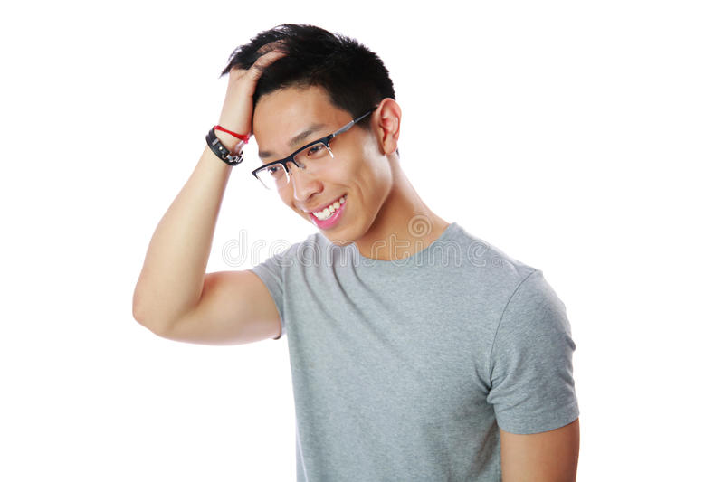 L'uomo asiatico felice tocca la sua testa fotografia stock