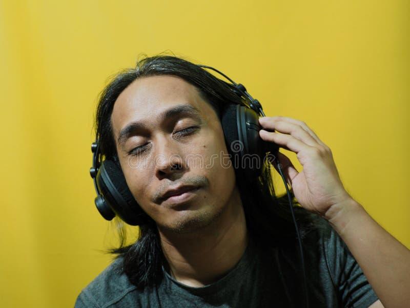 L'uomo asiatico mette le cuffie su fondo giallo immagini stock