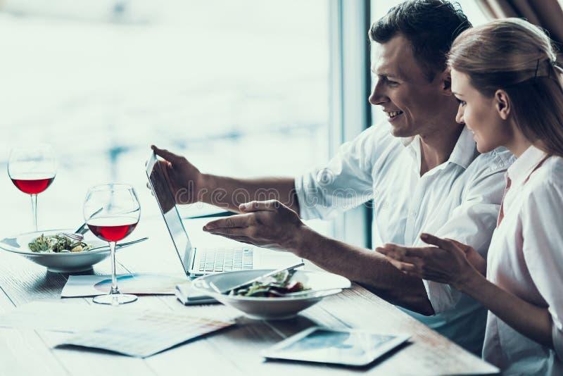 L'uomo astuto con la compressa si siede con la giovane donna in caffè fotografia stock libera da diritti