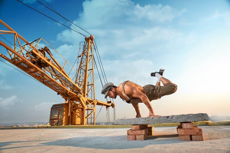 L'uomo atletico che fa l'esercizio spinge aumenta sulle mani fotografia stock libera da diritti