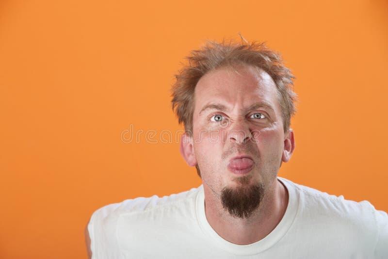 L'uomo attacca fuori la sua linguetta fotografia stock libera da diritti