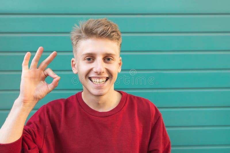 L'uomo attraente emozionale sorride e mostra un'APPROVAZIONE di gesto su un fondo del turchese immagini stock