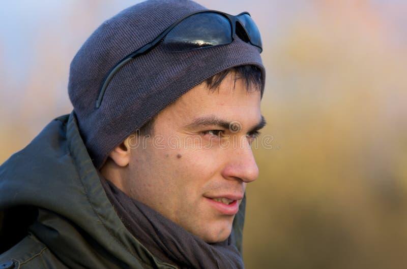 L'uomo attraente nell'inverno copre con gli occhiali da sole sulla testa fotografie stock