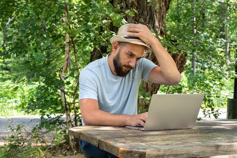 L'uomo barbuto è imbarazzato e pensa mentre lavora ad un computer portatile all'aperto fotografie stock libere da diritti