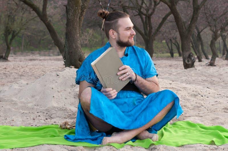 L'uomo barbuto bello con compone, panino sulla testa nella seduta blu del kimono, tenente il mistero fotografia stock