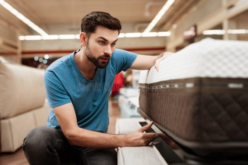 L'uomo barbuto bello sta provando il materasso in negozio di mobili Materasso ortopedico per una posizione sana immagine stock libera da diritti