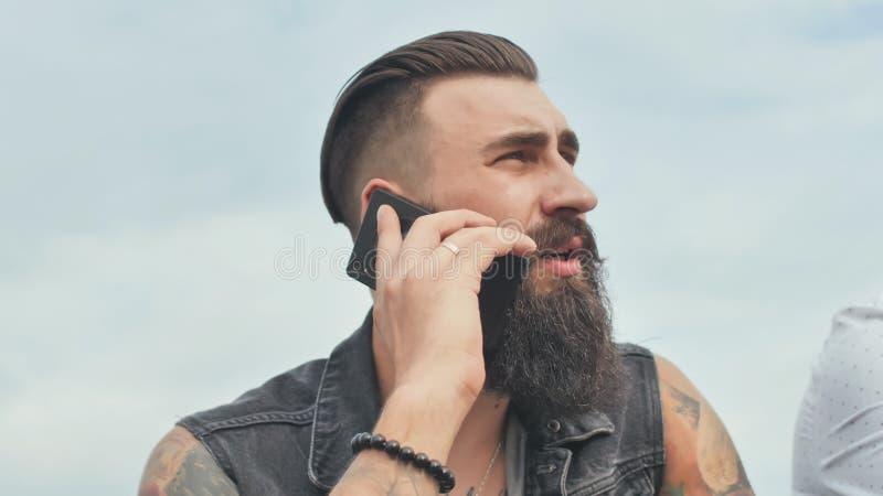 L'uomo barbuto brutale che parla sul telefono e fuma una sigaretta fotografia stock libera da diritti