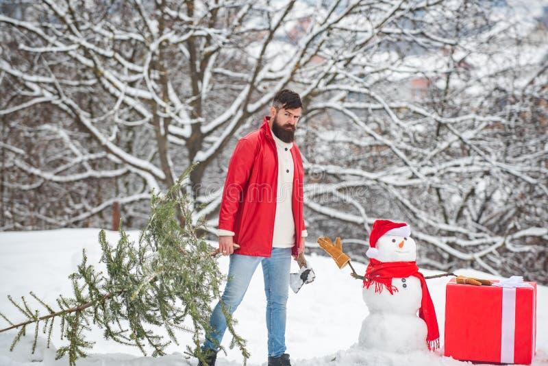 L'uomo barbuto con il pupazzo di neve sta portando l'albero di Natale nel legno Un giovane bello con l'uomo della neve porta il N fotografie stock