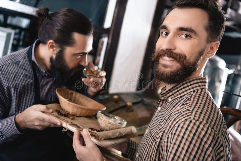 L'uomo barbuto contento dà l'uomo in grembiule ai coni di luppolo di annusata in fabbrica di birra della birra del mestiere immagini stock libere da diritti