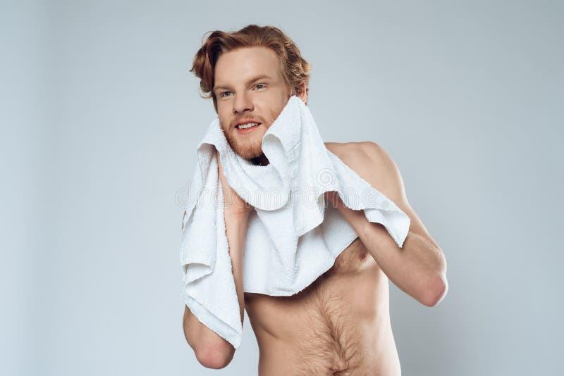 L'uomo barbuto dai capelli rossi pulisce il fronte con l'asciugamano immagine stock