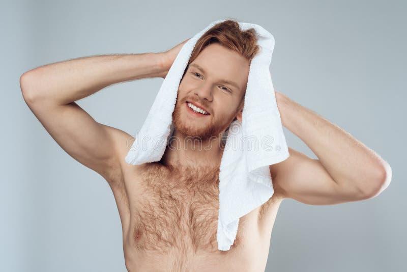 L'uomo barbuto dai capelli rossi sta pulendo i capelli bagnati dall'asciugamano immagine stock