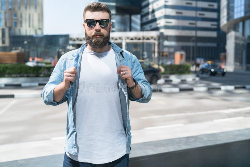 L'uomo barbuto dei pantaloni a vita bassa in occhiali da sole, vestiti in maglietta bianca, sta sulla via della città Derisione s fotografia stock