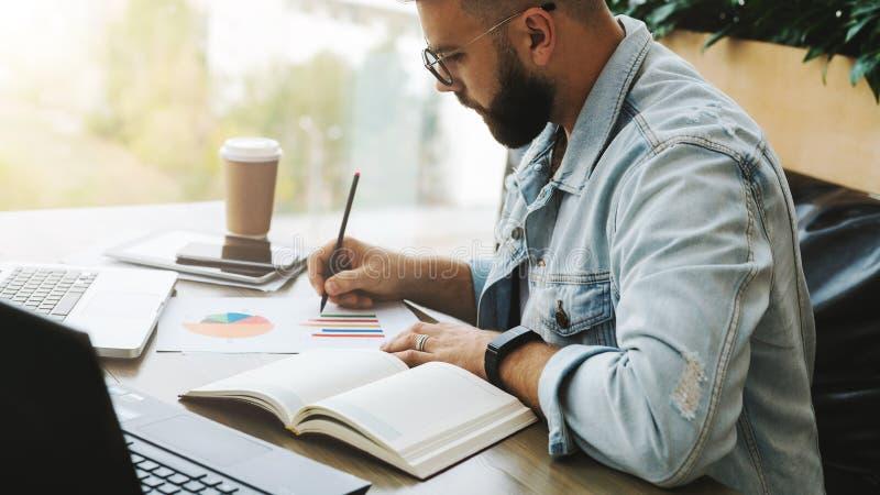 L'uomo barbuto dei pantaloni a vita bassa si siede alla tavola, lavorando al computer portatile e fa le note nel grafico, il graf fotografie stock libere da diritti