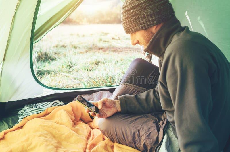 L'uomo barbuto del viaggiatore utilizza il suo telefono cellulare che si siede in tenda immagine stock