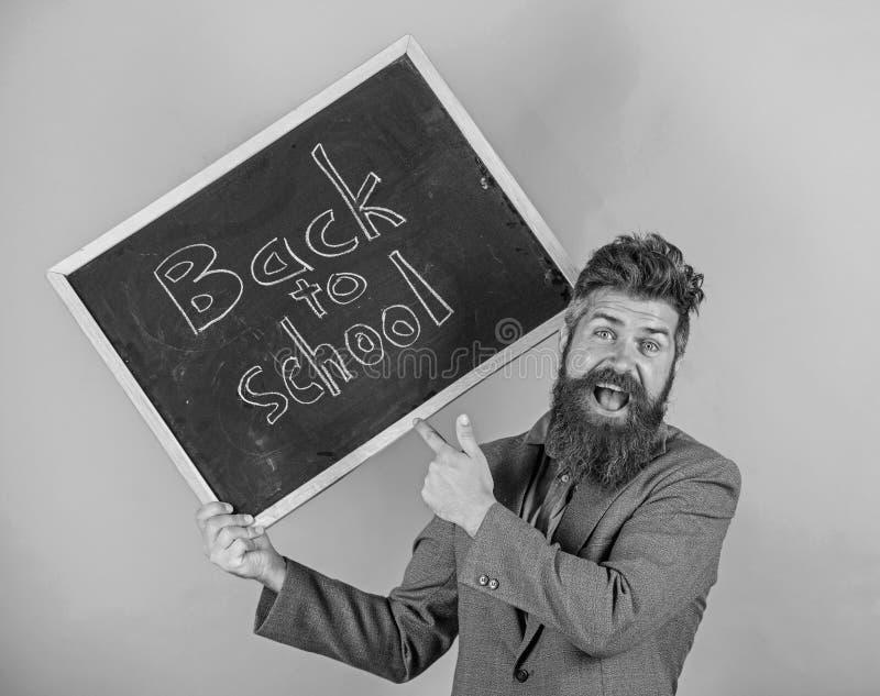 L'uomo barbuto dell'insegnante tiene la lavagna con l'iscrizione di nuovo al fondo di verde della scuola Inviti per celebrare il  fotografie stock libere da diritti