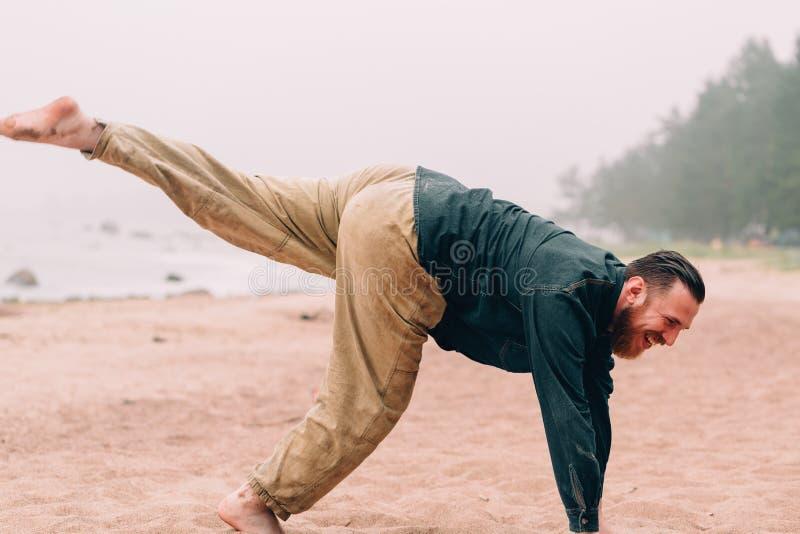 L'uomo barbuto felice fa gli esercizi di mattina alla spiaggia fotografia stock libera da diritti