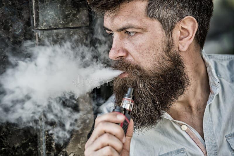 L'uomo barbuto fuma il vape, nuvole di fumo bianche Concetto elettronico della sigaretta L'uomo con la barba lunga sembra rilassa immagine stock libera da diritti