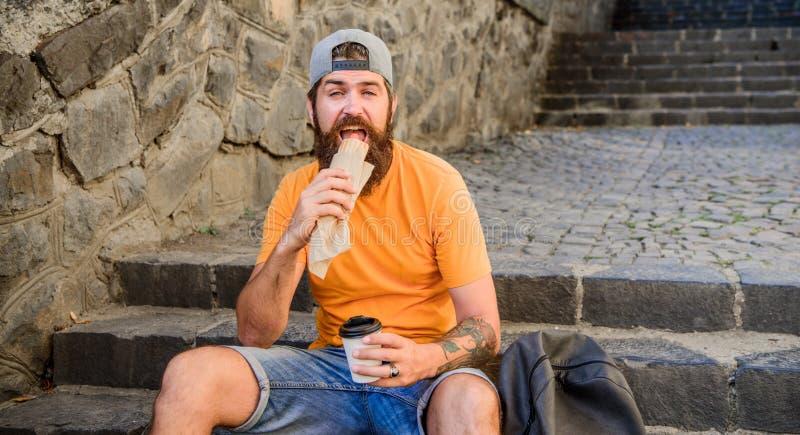 L'uomo barbuto gode rapidamente della tazza di carta della bevanda e dello spuntino Alimento della via cos? buon Nutrizione urban fotografia stock libera da diritti