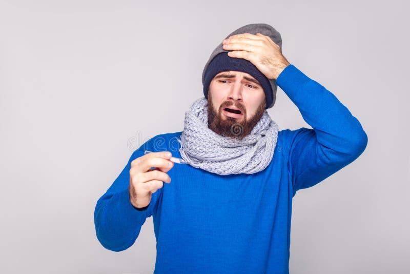 L'uomo barbuto malato indisposto ha temperatura, giudicante il termometro fotografie stock libere da diritti