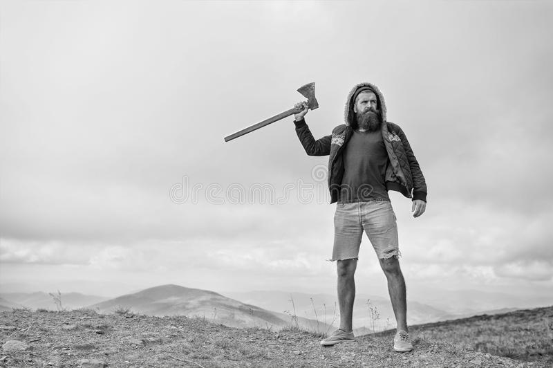 L'uomo barbuto, pantaloni a vita bassa brutali con i baffi tiene l'ascia sulla montagna immagine stock libera da diritti