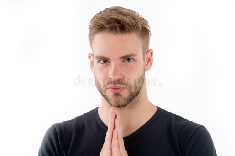L'uomo barbuto prega isolato su bianco La preghiera del tipo si tiene per mano afferrato vicino al fronte non rasato Concentrazio fotografia stock libera da diritti
