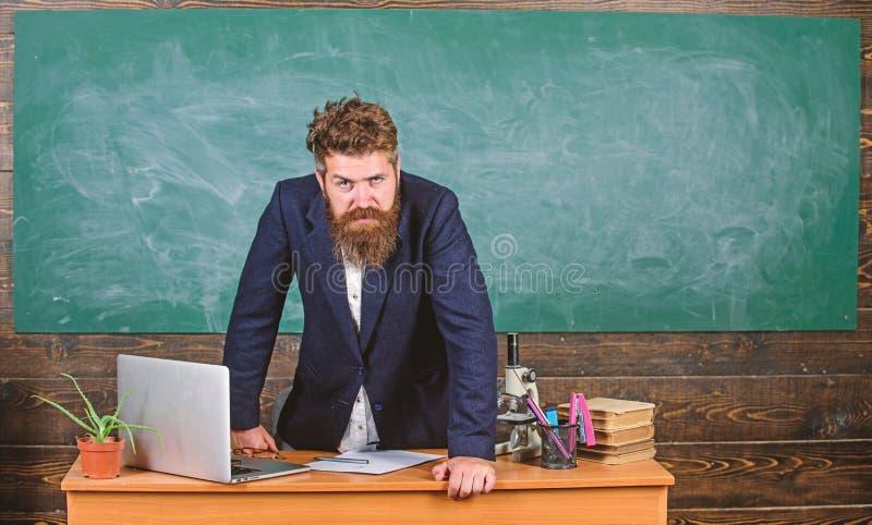 L'uomo barbuto serio rigoroso dell'insegnante si appoggia il fondo della lavagna della tavola Sembrare dell'insegnante che minacc immagini stock