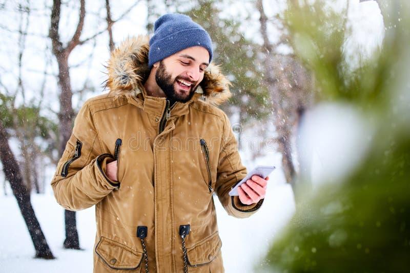 L'uomo barbuto sorridente indossa i vestiti caldi ed utilizzare dell'inverno lo smartphone con la connessione dati veloce di Inte fotografia stock