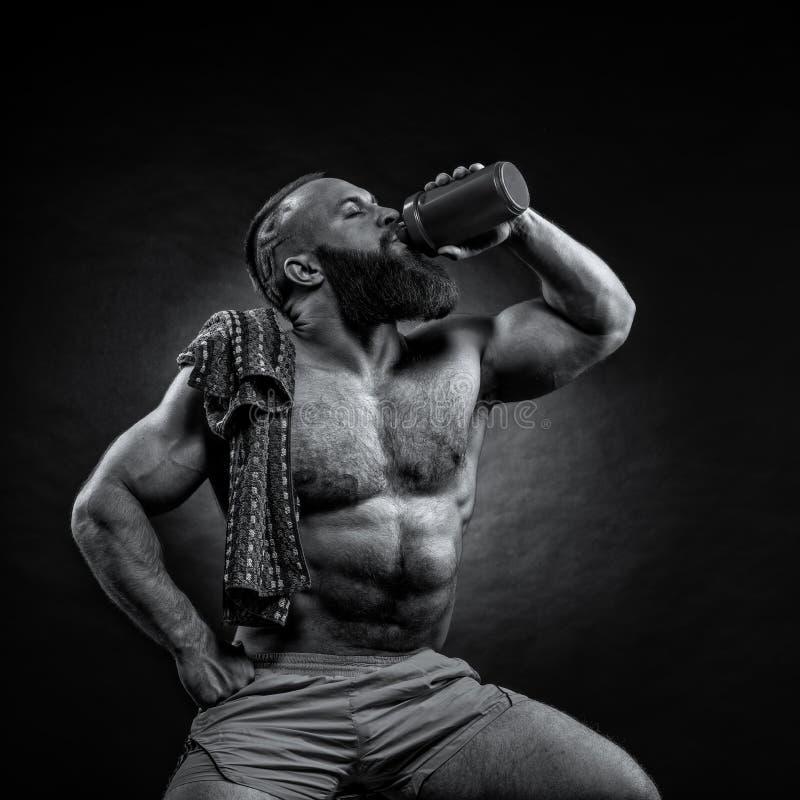 L'uomo barbuto sta tenendo un agitatore per le bevande immagine stock