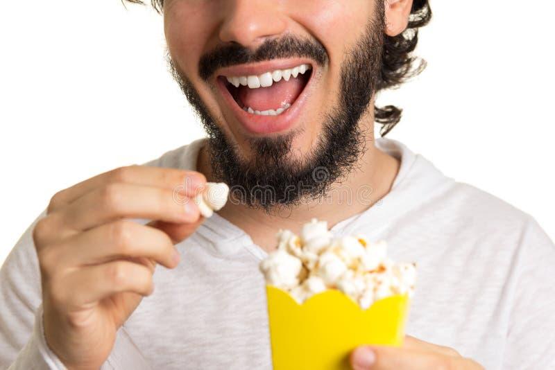 L'uomo barbuto sta tenendo un popcorn in sua mano Pacco di popcorn immagini stock