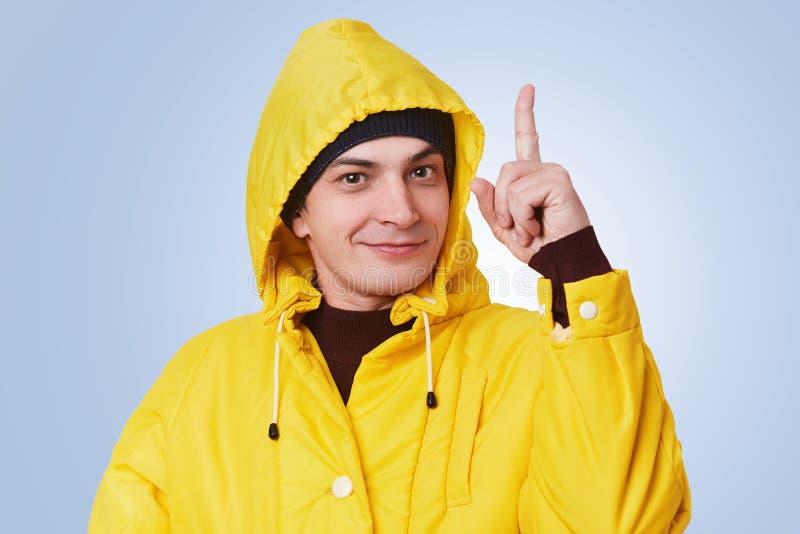 L'uomo bello abile alza il dito anteriore come ottiene idea brillante, porta l'impermeabile giallo, fa isolare l'espressione alle fotografia stock