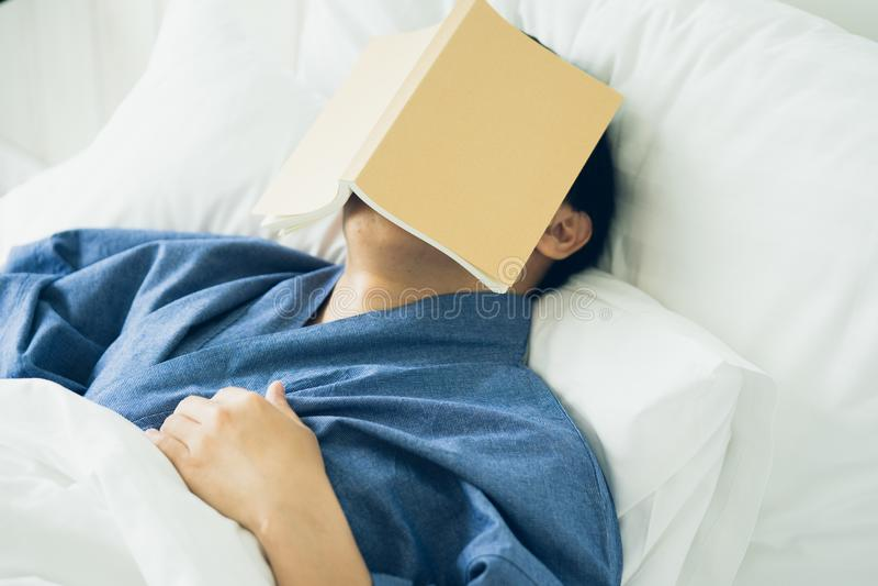 L'uomo bello asiatico ha letto i libri mentre dormiva La sonnolenza della copertina di libro dell'uomo causa il sonno Il concetto immagine stock