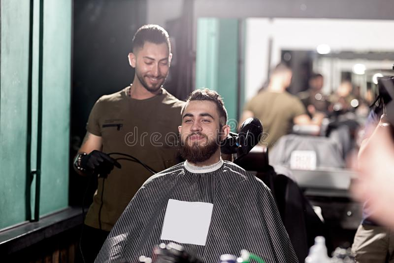 L'uomo bello con la barba si siede ad un negozio di barbiere nella parte anteriore lo specchio Il barbiere fa una disposizione de fotografie stock