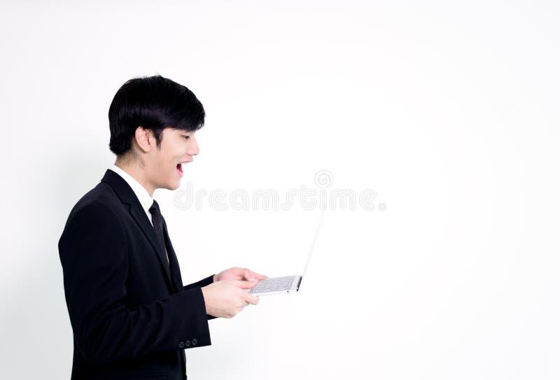 L'uomo bello di affari asiatici ha computer portatile della tenuta per woking con la h immagine stock