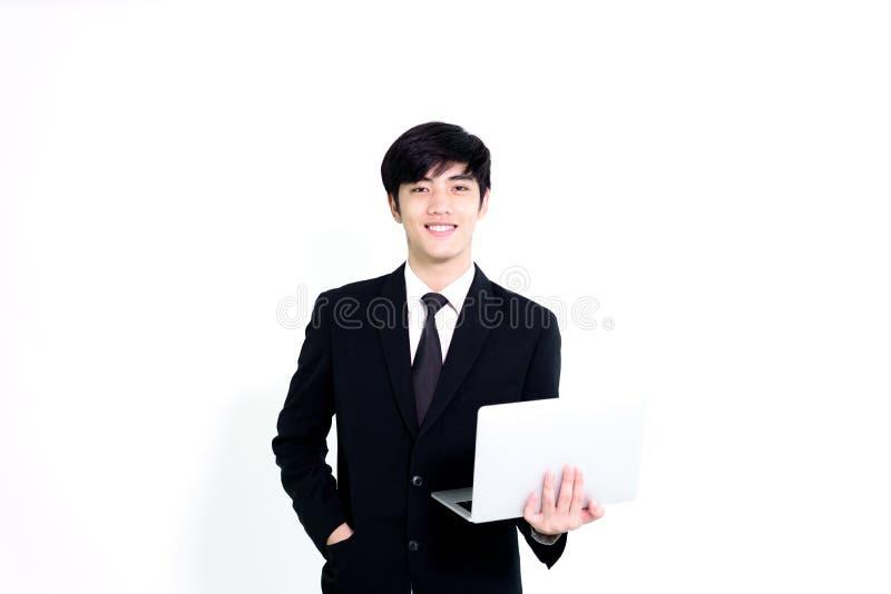 L'uomo bello di affari asiatici ha computer portatile della tenuta per woking con la h fotografia stock libera da diritti