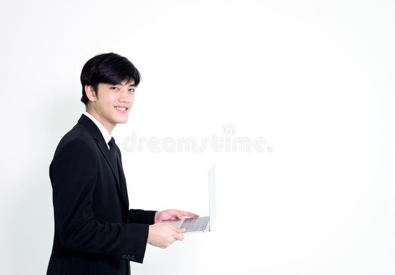 L'uomo bello di affari asiatici ha computer portatile della tenuta per woking con la h fotografia stock