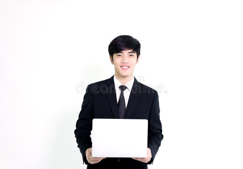 L'uomo bello di affari asiatici ha computer portatile della tenuta per woking con la h fotografie stock libere da diritti