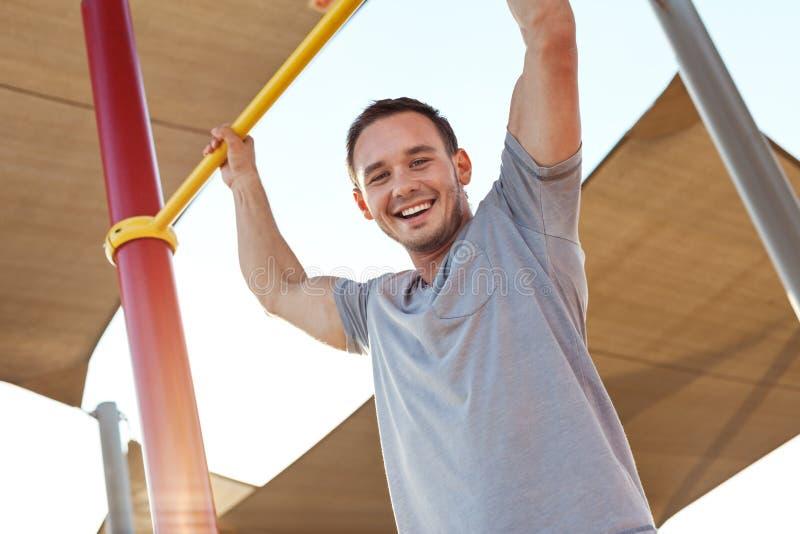 L'uomo bello e lo sport si esercitano sulle barre orizzontali fotografie stock