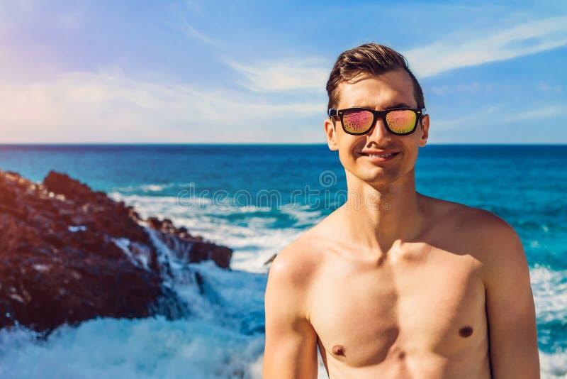L'uomo bello felice cammina sulla spiaggia dagli occhiali da sole d'uso del tipo sexy topless della costa di mare fotografia stock libera da diritti