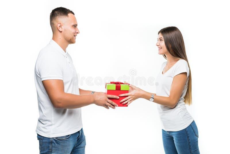 L'uomo bello rende presente alla sua amica, isolata su fondo bianco immagine stock