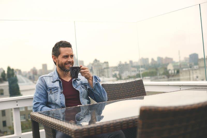 L'uomo bello sta bevendo il caffè in caffè fotografia stock libera da diritti