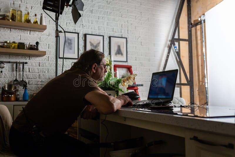 L'uomo bello sta lavorando nel centro dati con il computer portatile immagine stock libera da diritti