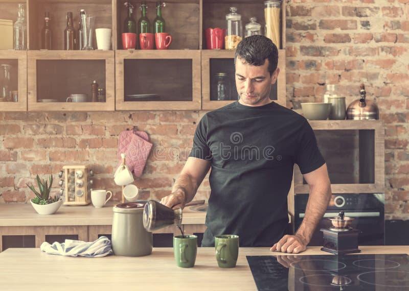 L'uomo bello versa il caffè di recente preparato nelle tazze immagine stock libera da diritti