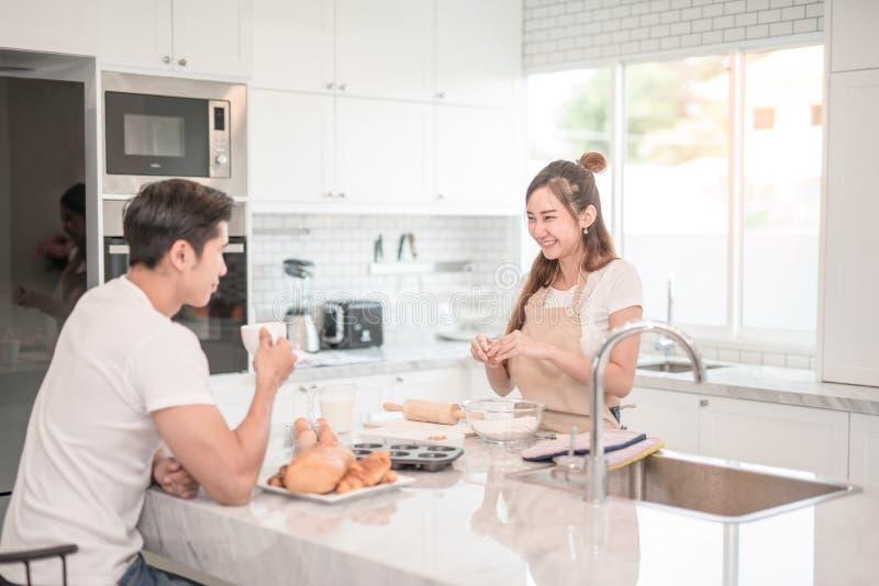L'uomo beve il caffè mentre una donna prepara un pasto fotografia stock