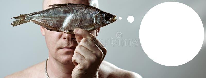 L'uomo brutale calvo con un torso nudo tiene un pesce essiccato davanti al suo fronte fotografia stock libera da diritti