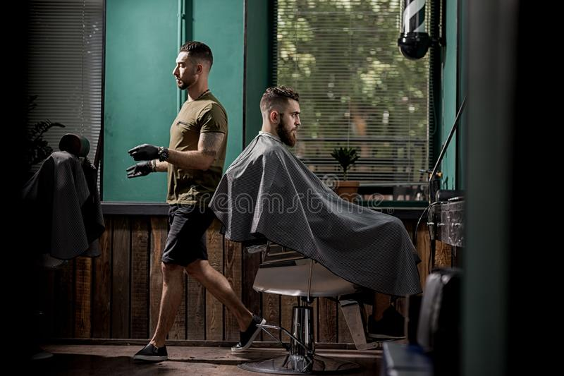 L'uomo brutale con la barba si siede in un chire ad un negozio di barbiere Il barbiere bello passa accanto lui fotografie stock libere da diritti